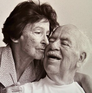 Lightly sepia toned black & white portrait of an elderly couple; the dark-haired woman and the white-haired man holding their cheeks together.