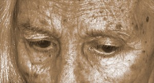 Sepia-toned black & white photographic close-up of a woman's forehead and eyes.
