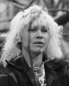 Black & white portrait of a woman with long, wavy blonde hair.