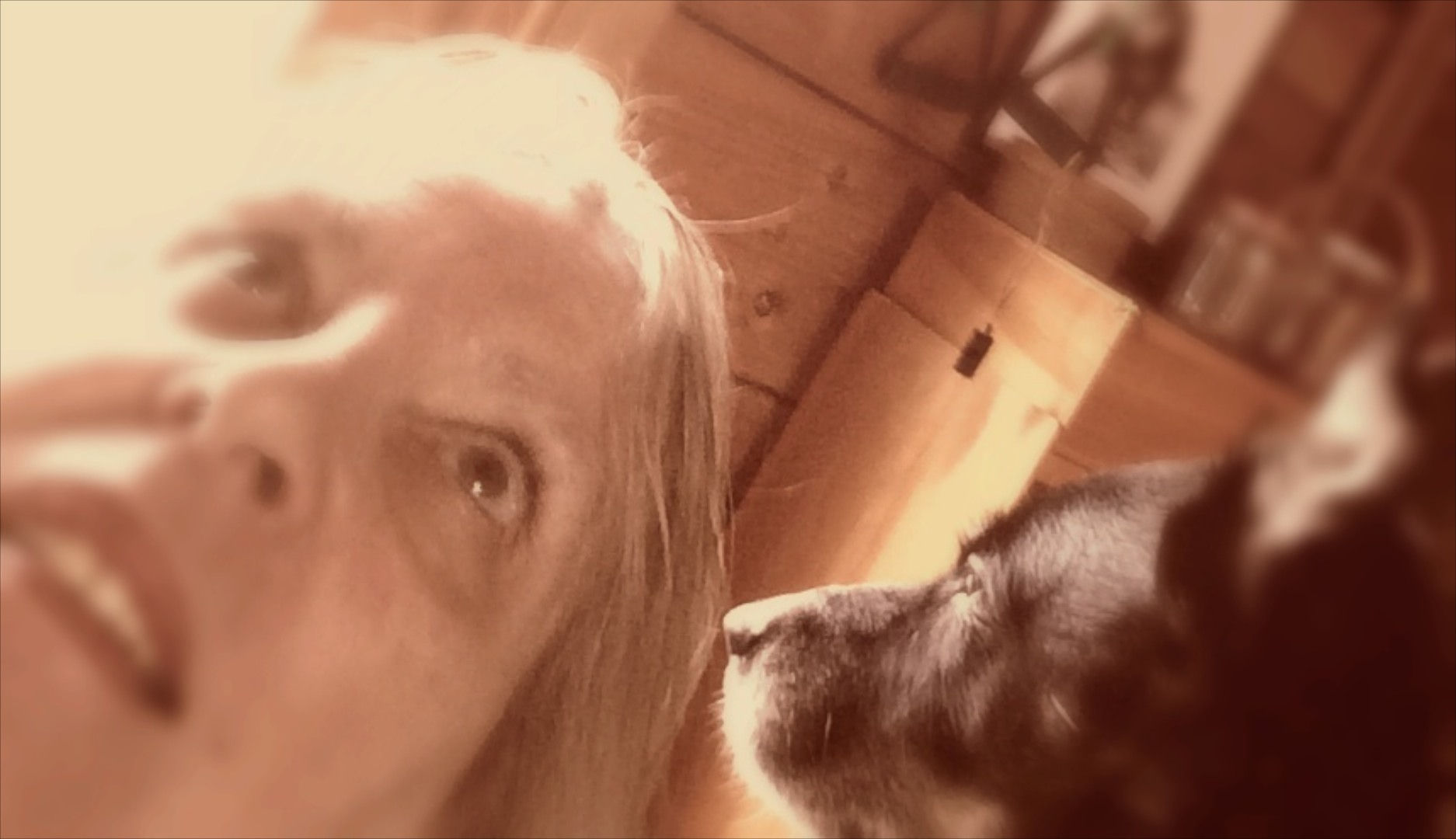 Lightly sepia tinted color selfie of artist Mignon Naegeli and her dog Basquiat.