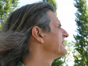Color photograph head shot in profile view, prominently showing the artist's beautiful long hair, with trees in the background.