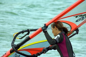 """Color photograph of a female Wind Surfer on Lake Morat, Switzerland. Still picture, shot during the filming of the short """"Teasing the Wind"""" by Mignon & Wolf Naegeli."""