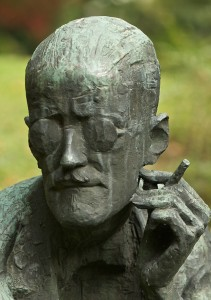 Color photograph of Milton Hebald's bronze statue of James Joyce at Fluntern Cemetery in Zurich, Switzerland. The detail shows the spectacled head of the writer and his left hand holding a cigarette.