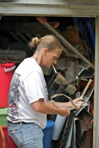 Color photograph of woman recycling aluminum scraps from a construction site.