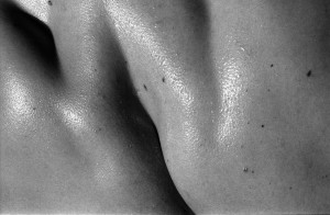 Black & white photograph of glistening skin on a muscular back.