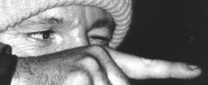 Black & white closeup of the eyes and hairy hand of a man wearing a light-colored knitted hat. He appears to be aiming a bow and arrow, with his left eye closed and the right eye peering along his stretched out right index finger.