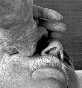 Black & white close-up photograph from below the chin of a man holding his left hand against his right cheek. The bent fingers are touching the nose and appear to be crippled by arthritis. Above a short gray mustache stand out the nostrils and the eyebrow and lashes of the left eye.