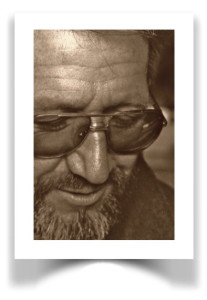 Close-up sepia toned black and white photograph of a bearded man wearing eyeglasses..