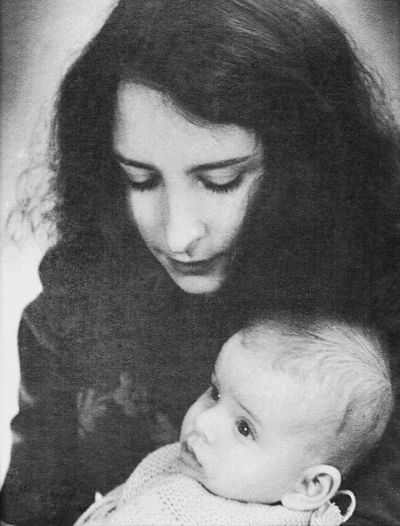 Black & white closeup of a black-haired woman holding an infant.