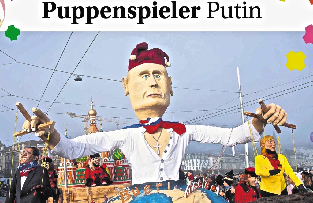 Color photograph of a parade float with an effigy of Vladimir Putin holding string puppets resembling Baarak Obama and Angela Merkel