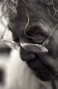 This black & white closeup portrait photograph is an artistic shallow-focus impression of Hans Erni at work in his studio. The view is on his left temple from an approximately 45 degree angle between front and side. His head is tilted forward and he is looking down. In focus are primarily a big curl hanging over his forehead, a narrow long strand of gradually curling hair extending even beyond his left eyebrow, and the top left corner of his glasses.