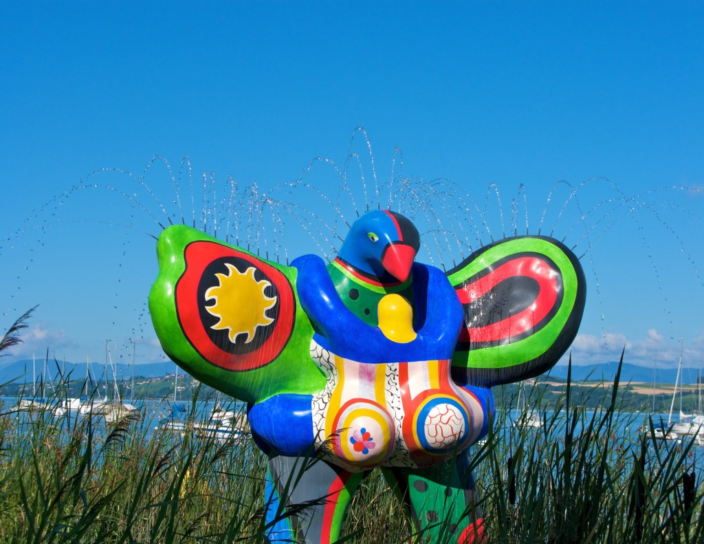 Color photograph of the Nana fountain/sculpture, which stands in an expanse of reeds with anchored sailboats in the background. The huge, colorful sculpture of a voluptuous woman/angel/bird has water jets along the upper edge of its wings and on top of its bird head. Lime green, royal blue, and fire-engine red colors dominate on the glossy surface of the huge polyester sculpture.