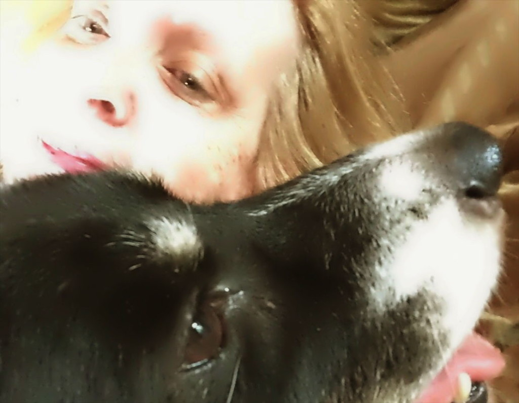 Detail color photograph of a black dog's eyes and snout in right profile view close to the chin of a blonde woman's head in oblique frontal-left view. The dog has a white-tipped muzzle and a white spot over the eye. The dog's hazelnut eye color is just a bit darker than the woman's.