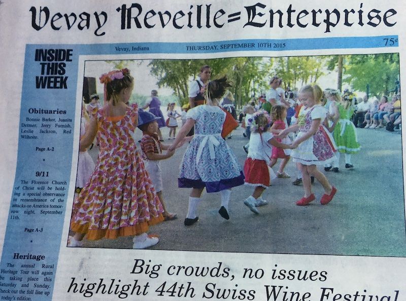 Detail from a Vevay Reveille-Enterprise cover, showing the masthead and a color photograph of costumed adults and children in the city park with the Ohio River as a backdrop. The children are dancing in pairs holding hands while onlookers are seated on the fringe. The headline below reads: Big crowds, no issues highlight the 44th Swiss Wine Festival.