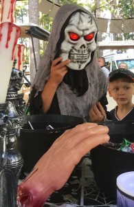 Color photograph of a tall person clad in black, with gray gauze draped over the head, shoulders, and chest, wearing a white skull mask with large, red-glowing illuminated eyeballs who is standing between large metalized gothic horror candelabra and an unmasked small boy, who appears to be clinging to the tall person for reassurance. They are looking at black buckets full of treats on a table in front of them. A very large chopped-off plastic hand rests on the rim of one of the buckets.