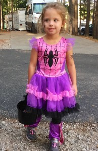 Photograph of a little girl in a ruffled pink and purple costume with a big stylized black widow spider on the chest and spider tatoo stickers on her right cheek and left upper arm. She carries a small black bucket to collect treats.