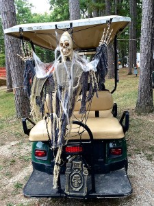 Color photograph facing a cone-headed skeleton that is attached to the back of a six-seat golf cart. It holds up its skeletonized hands and is draped in shaggy black rugs, beige gauze, and fake white spider webbing. Black plastic spiders seem to be crawling up on it from a miniature plastic headstone embossed with a skull and RIP scroll.