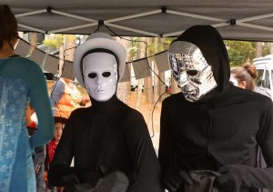 Color photograph of the chests and heads of two people holding black bags who are wearing tight fitting black jump suits with seamless gloves, hoodies, and face cover. One wears a white rimmed melon hat and shiny white mask, the other a chrome mask with embossed reticulum. There seems to be nothing behind their large eye openings; only black!