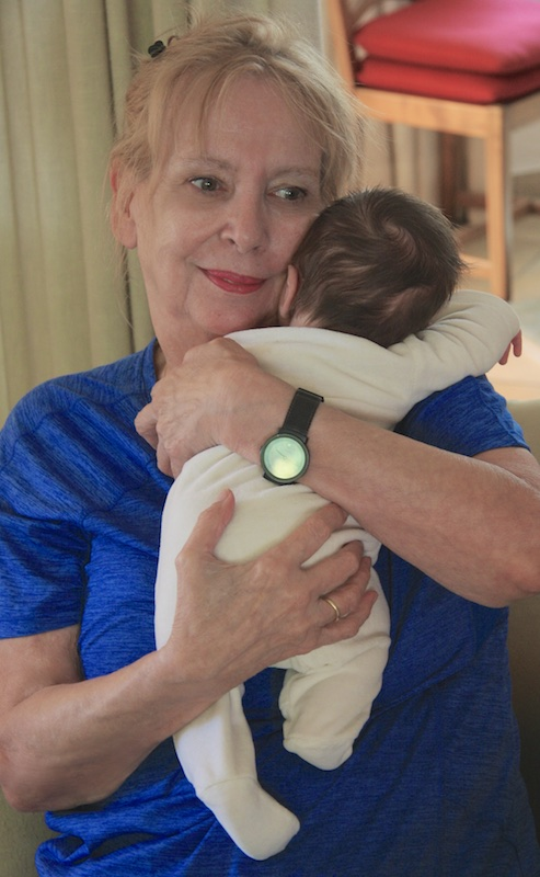 Color photograph of a woman in a blue shirt huging a newborn whose right arm and head are resting on her left shoulder. His left ear and dark brown hair are pressed against her left cheek.