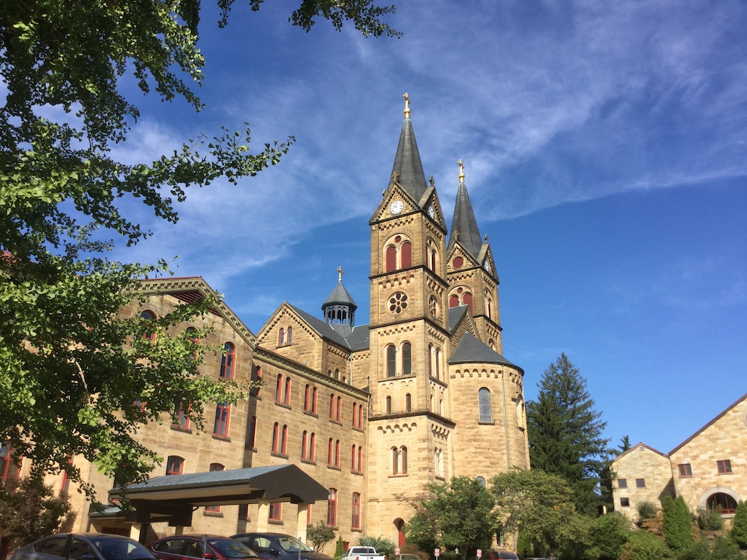 Color photograph of the Saint Meinrad Archabbey church at the center with the two main towers, big apse between them at the east end, and the small crossing tower visible in the back. To the left is St. Anselm Hall of the Seminary & School of Theology with the long canopy of the Health Services entrance and some cars in the foreground. At right, detached from the church, is the south-west corner of the Monastery.