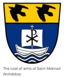 Coat of arms of Saint Meinrad showing two stylized black falcon silhouettes on yellow background in the top third and a stylized sailboat crossing wavy waters on blue background in the lower two thirds of the shield.