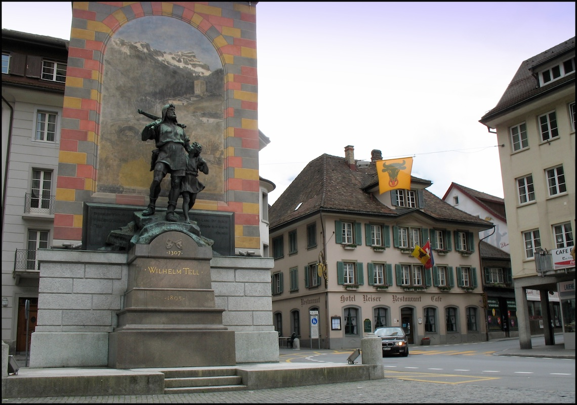 Color photograph of the Wilhelm Tell monument in Altdorf, Switzerland. The bronze statue is displayed in front of a painting of a