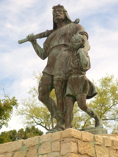 Color photograph of a bronze statue depicting a walking man, holding in his right hand a crossbow that rests on his shoulders. He is guiding a young boy whose left shoulder he holds with his left hand. The boy has placed his own left hand over the man's, and he is leaning his right shoulder against the man's hip. The man's left leg and the boy's right one are stretched straight in mid-stride, while their other legs are angled behind them. One cans see the boy's left toes just about to be lifted off the ground for the next step. The statue stands on a crude platform of irregular sized and shaped rectangular limestone blocks held together by a shoddy looking mortar job.The chestnut colored bronze is weathered irregularly, with greenish streaks and spots.