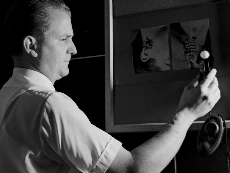 Black and white photograph showing a right head and chest profile view of James Perret wearing a short-sleeved white shirt in a dark room. He is watching an incident-light meter that he hold in front of a framed pasteboard where one can barely make out a couple of attached photographs. Directional lighting from the right dramatically emphasizes his silhouette, right side of face and right ear as well as his angled right arm and the white semi-spherical sensor of the meter he is holding up.