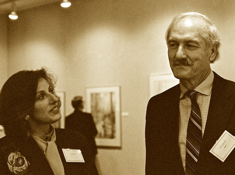 Sepia-toned black and white photograph of a dark-haired woman looking up to a tall, white-haired man who could probably rest his chin on the top of her head if they were standing much closer together. Visible in the soft-focused background between them is an art gallery wall with a person looking at one of the pictures.
