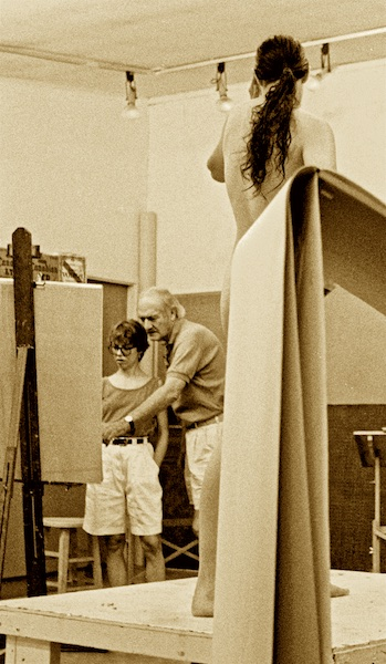 Sepia-toned black and white photograph of an art studio. At left we see the back side of an easel, in front of which are standing a woman and a tall man. He leans forward, pointing at something on the easel. At right we see the top of a flip-chart-style easel with tall used sheets hanging down toward us almost like a waterfall. These sheets obscure our view of the lower back of a model with a very long dark pony tail. She is standing on a low, white platform in the center of the room. Only slivers of her lower torso, right leg, and left toes are visible beyond the edges of the sheets.