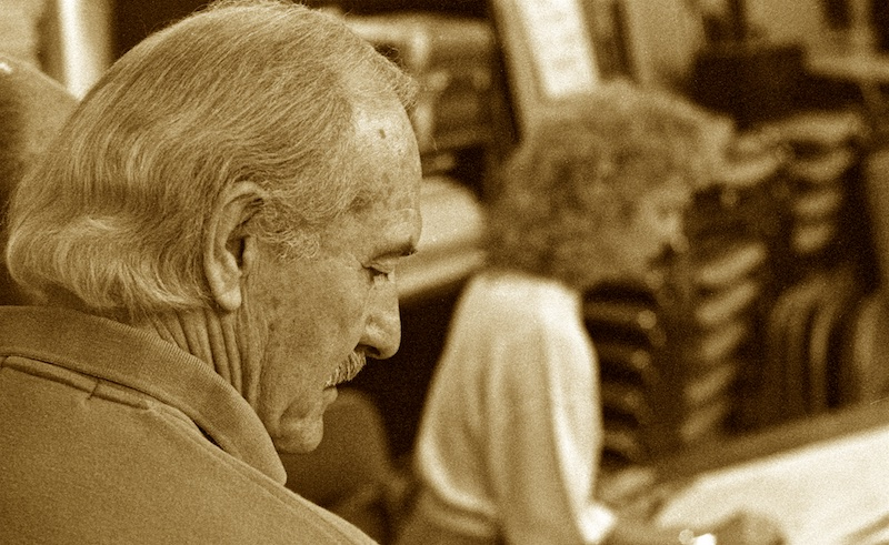 Sepia-toned black and white profile portrait shot from the back over the right shoulder of a mustached man, who has a thinning hair line but very full, wavy hair on the back of his head. The soft-focused background reveals an art studio and a woman working on a drawing board.