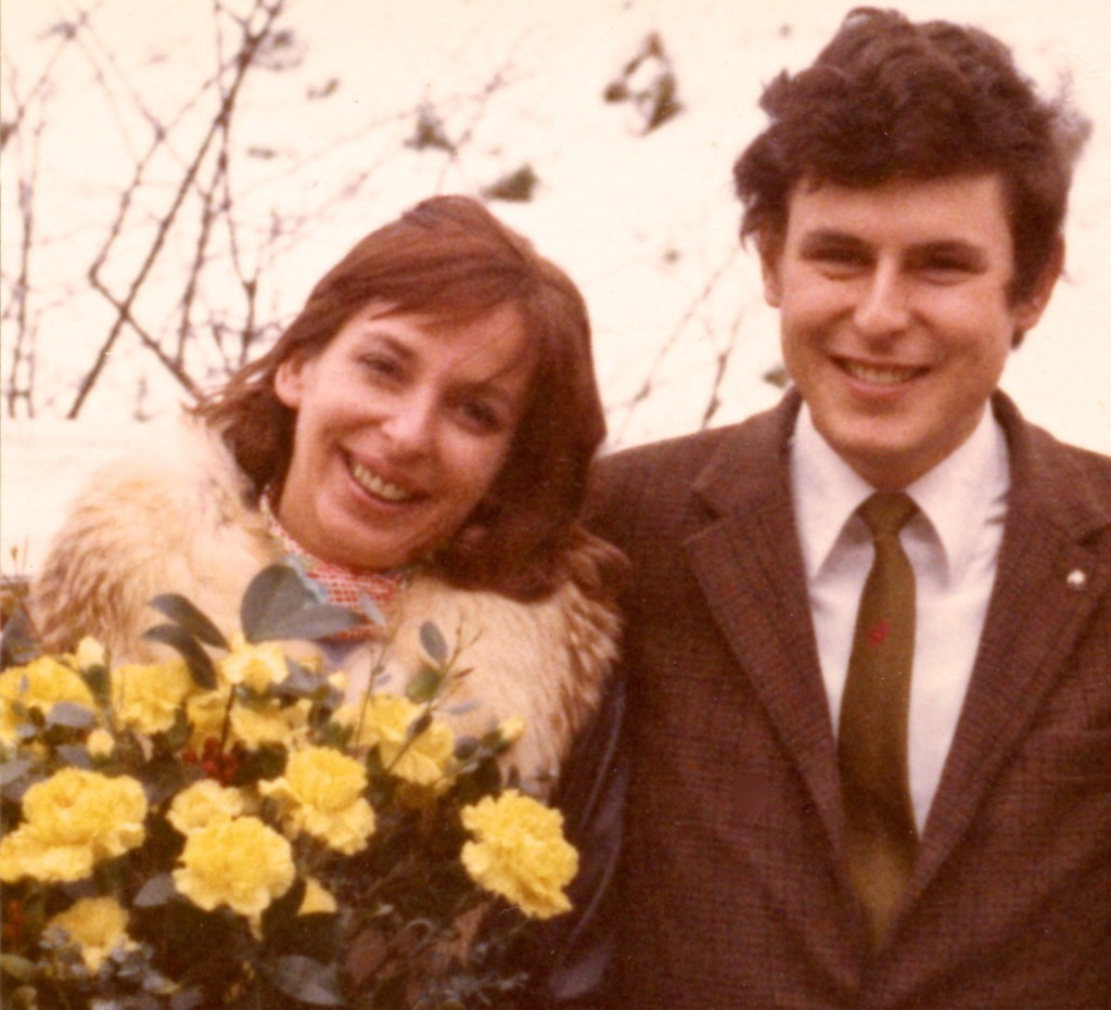 Color photograph of a couple with happy faces. The female is holding a bouquet of yellow roses.