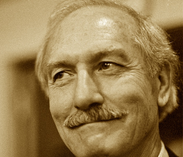 Sepia-toned black and white portrait of a man with a mustache, lively eyes, and a broad smile.