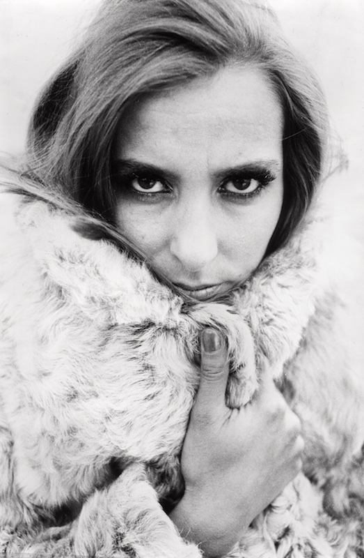 Black and white portrait of a young woman clasping the broad collar of her light-colored fur coat in front of her chin. Her right thumb with glossy finger nail is straight up and almost reaches her lips in front of the right side of the collar, which covers the lower part of her right cheek and extends up to her cheekbone. The ears are hidden by straight, fairly dark hair. With her head slightly bent downward, she glances straight into the camera, which causes broad white bows of her sclerae to contrast strongly with the dark areas comprising her eyebrows, upper eyelashes, and mid to lower visible pars of her irises.