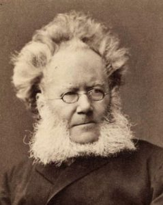 Sepia-toned black and white portrait photograph of a man with unruly hair (even more reminiscent of Albert Einstein's) and a square white beard spreading out from the cheeks and below the chin. He is wearing oval, wire-framed glasses and a dark jacket.