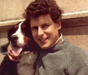 Color portrait of a Bernese Mountain Dog head to head next to a man, who has his right arm wrapped around it's shoulders and his hand petting it's muzzle. The man has curly brown hair and wears a gray, knitted, warm sweater over a beige polo neck.