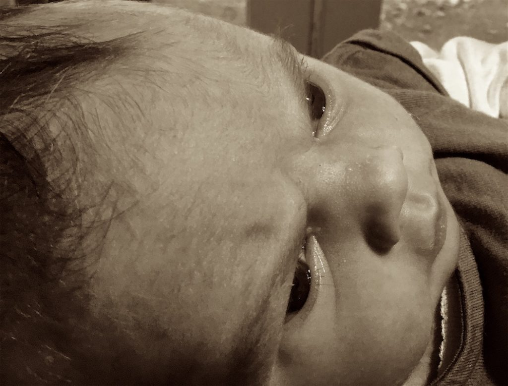 Black and white sepia toned photograph of a baby's head.