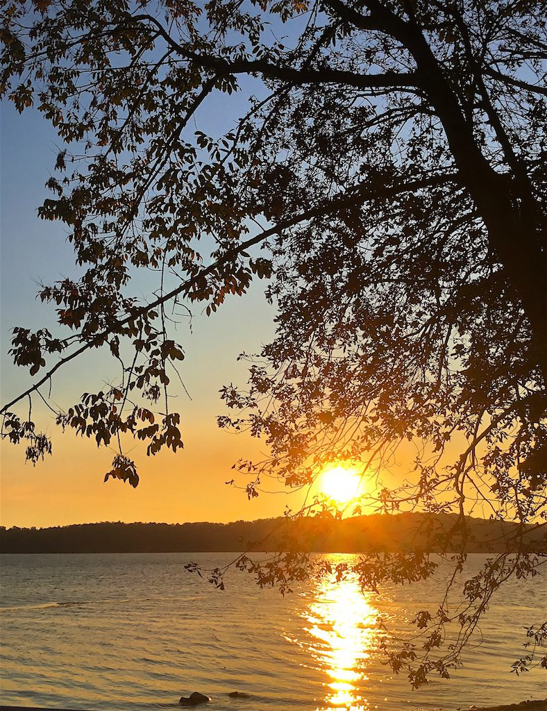 Color photograph of a sunset with a long, strong reflection on a lake. The sun appears as a bright golden ball just above a wooded ridge on the other side of the lake. The scene is viewed through branches of a deciduous tree. The sky that is bright orange over the horizon fades up to a light blue at the top of the image.