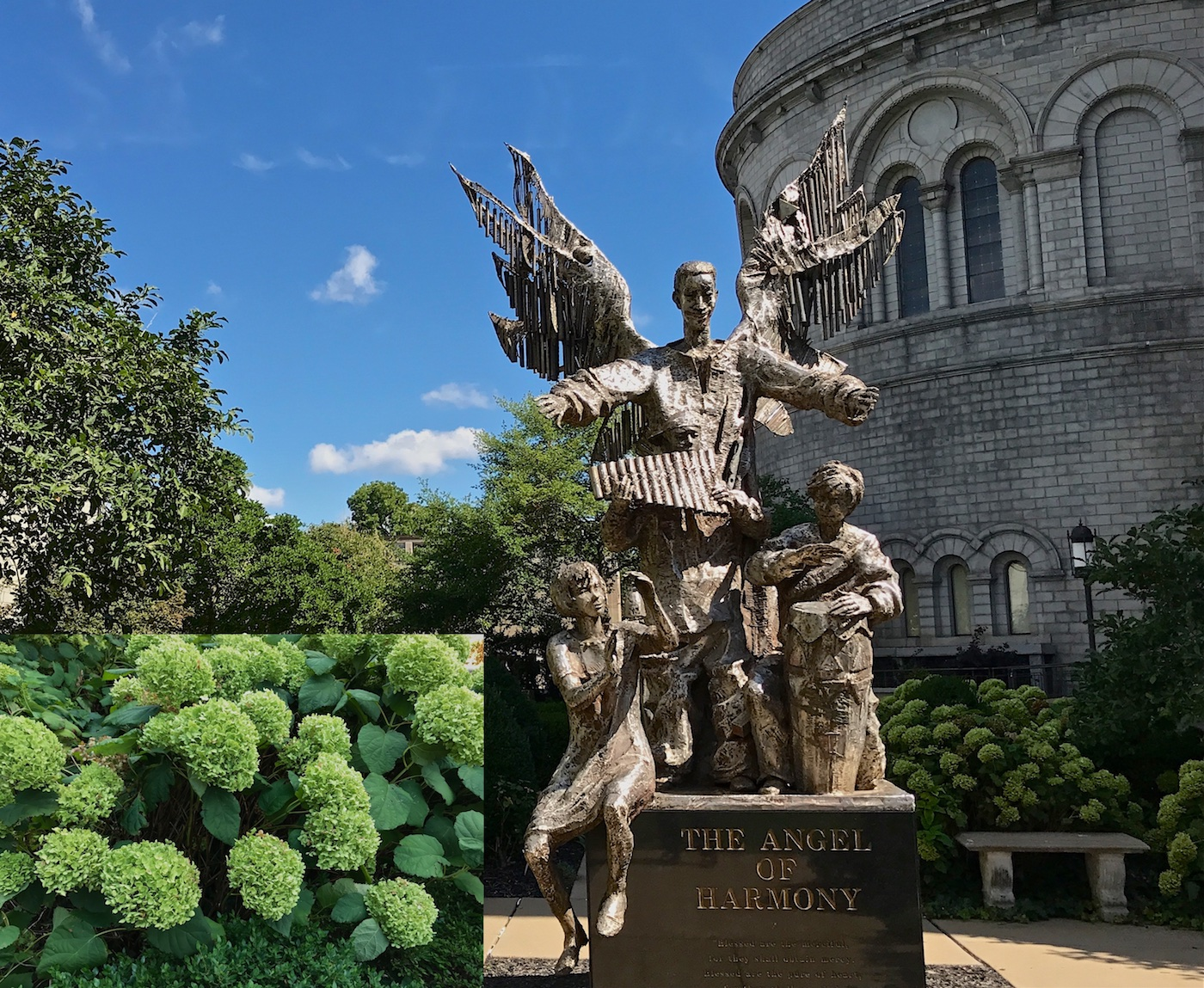 Color photograph showing a bronze sculpture of an angel whose wings are made of many loosely attached pipes that ring pleasantly in the wind. Three children are playing instruments under the stretched out arms in front of the angel. A boy standing in the center plays a pan flute. On his right side, a girl with a bell sits on the ground plate of the sculpture, letting her legs dangle over the sides of the black marble pedestal. On the opposite side a boy plays a tall conga drum. Green flowering hortensia provide the backdrop for the sculpture. A close-up photograph of them is inset at the bottom left corner of the image.