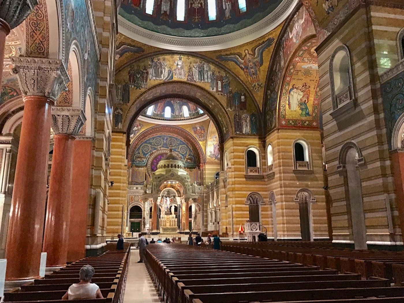 Color photograph of the Cathedral Basilica of Saint Louis. View of the interior of the nave toward the sanctuary. At the top, some of the windows of the central dome and the sanctuary dome are visible along with many of the glass mosaics.