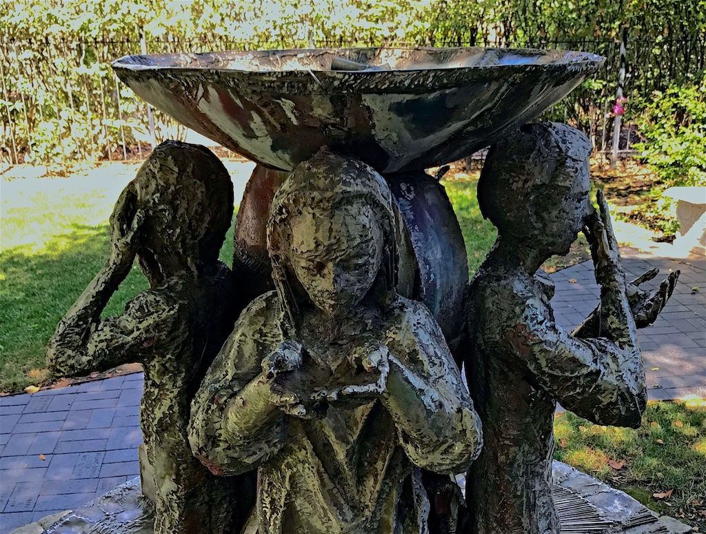 Color photograph of a bronze sculpture fountain. Three human figures stand under a large bowl that rests on an arch against which they are leaning. The figure fronting the camera is looking into her hands that she has bowled at chest height. The figured at left has the hands against the forehead. The figure at right touches the nose with the right hand and holds the open left hand up and forward at chest height.