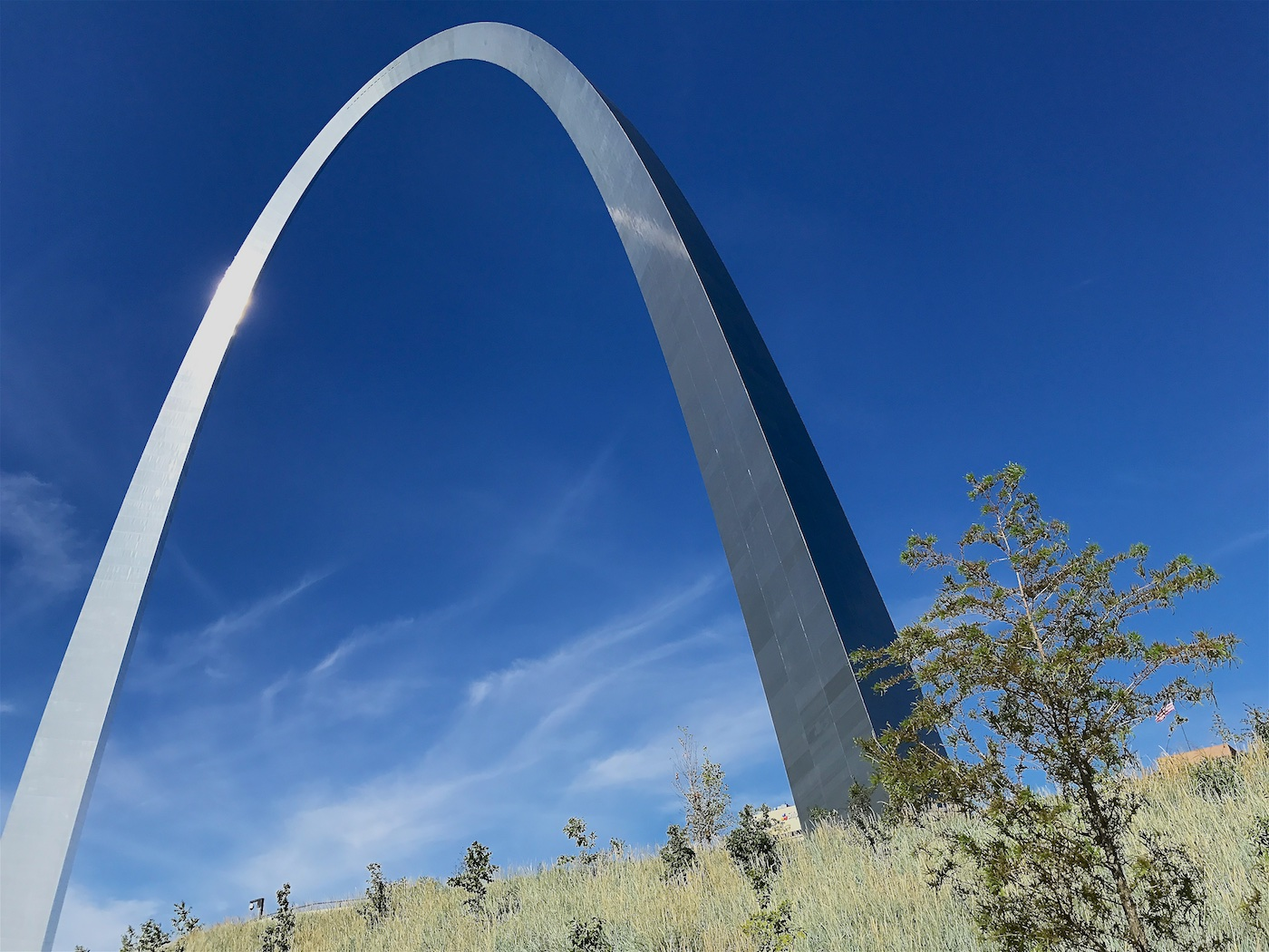 Color photograph of the Gateway Arch in Saint Louis, MO, from the northeast side against a dark blue sky with approaching cirrus clouds on the horizon. Above the grassy slope with scattered young trees in the foreground, a U.S. flag can be spotted in the distance at the right edge of the picture. A glistening sunspot on the shiny stainless steel south leg of the arch creates a bright secondary streak reflection on the east side of the north leg.