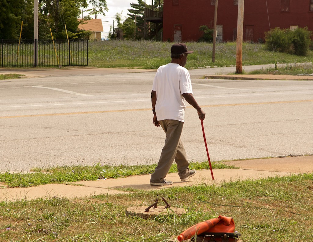 Color photograph of an African American man walking along a wide street on a sidewalk. He wears what looks from behind like a UPS driver's cap, a white short-sleeved T-shirt, khaki pants, old tennis shoes, and he uses a red walking stick. On the grass between him and the camera is a small round concrete foundation with three nearly foot-long bent, rust irons sticking out of it. Next to it is a similar obstacle, but covered with a crumpled, run-over orange hazard cone. On the other side of the street is a dark red, boarded up apartment building.