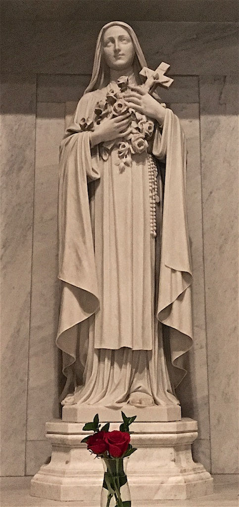 Tall marble statue of a woman in nun's robes, holding in her arms a cruzifix and a bouquet of roses. A rosary is hanging from her left hip. In front of the octagonal pedestal is a transparent glass vase filled with water. Two red roses and a few green leave are in view.