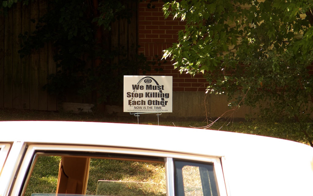 """Looking from the street over the roof of a parked car a sign is seen on a narrow strip of grass in front of a House. It reads, We Must Stop Killing Each Other,"""" and below, in smaller type, but capitalized and underlined, """"NOW IS THE TIME."""""""