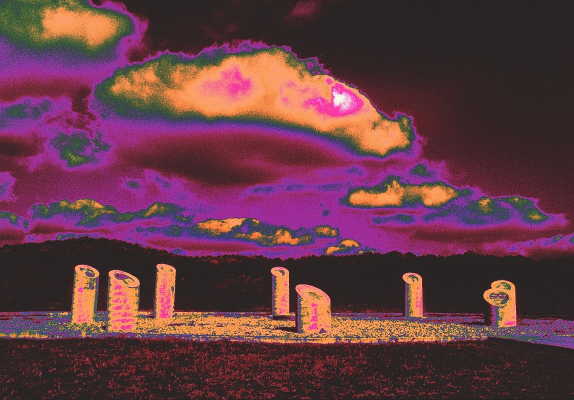 Photodigital interpretation of the Chota Monument. Purple, burgundy, ocre, and green colors dominate, often blending into each other, particularly in a sky with purple and green-rimmed clouds. On the ground, eight round pillars in mostly bright ocre tones are arranged in a circle. They resemble tall tree stumps that have been cut at an angle slanted toward the viewer. These oval surfaces seem to depict a variety of abstract, irregularly shaped patterns.
