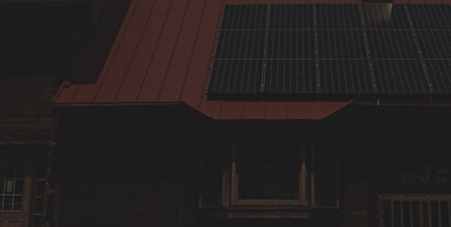 Color photograph of a house with a red metal roof on which an array of solar panels is mounted. The picture is quite dark as it was taken with normal settings when the moon covered about 99 percent of the sun, which was near the peak of the eclipse at this location. Thus, it provides a rendition of how little light remained.