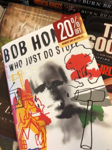 Color photograph showing the jacket of Sean Penn's book Bob Honey Who Just Do Stuff, A Novel, on top and in front of other recently released books. A sticker attached to the top right corner reads 20% off and in smaller print Members Save an Extra 10%.
