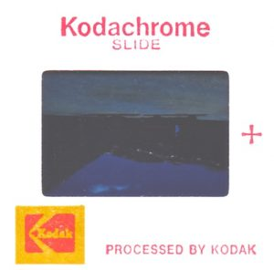 Color photograph of the back side of an original 1979 Kodachrome color slide. The red inscription at the top reads, Kodachrome SLIDE. At the bottom left is the red and yellow Kodak logo and next to it are the words PROCESSED BY KODAK. To the right of the film window is a red plus sign. The image is upside down with the emulsion facing us, as we are looking at it from the position of a projection lamp. The projection lens would be on the opposite side of the slide and invert the picture bottom to top and left to right so it will appear correctly on a reflective screen.