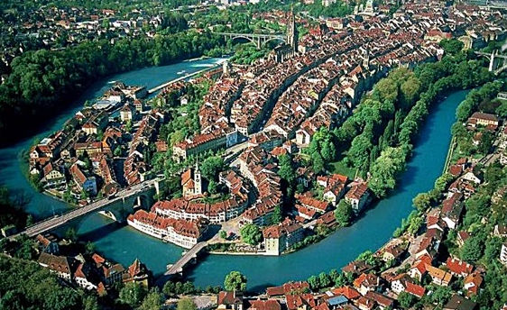 Color aerial view from the north-east on the great oxbow of the Aare river that hugs the old city center of Bern. It shows the high density of buildings on top of the hill and along the street that winds down to the Matte, the alluvial plain and point on the south-east inside of the bend.